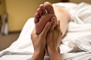 Two hands giving reflexology to foot